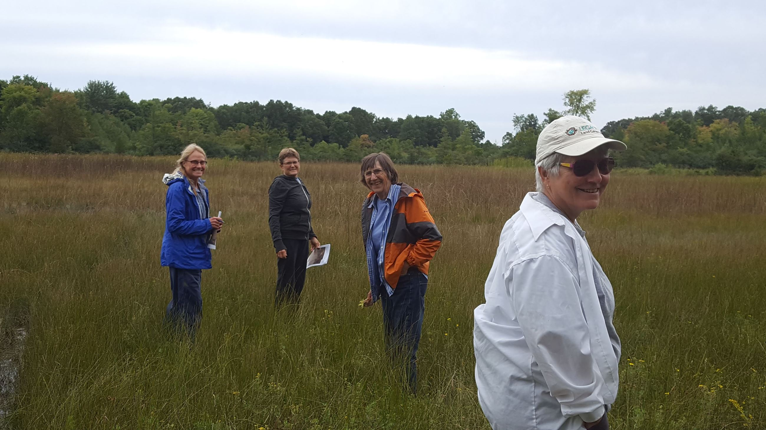 Members of NATAC in a wetland, smiling at the camera Opens in new window