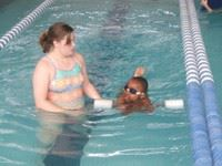 Swim instructor teaching child in pool