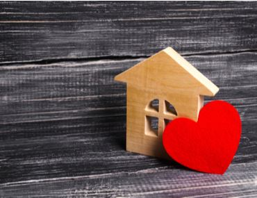 Image of a wooden block shaped like a house with a heart leaning against it.