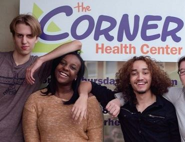 Photo of four teens smiling in front of the Corner Health Center sign.