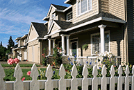 Image of a home behind a white picket fence