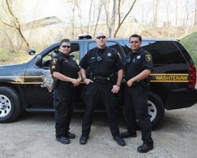 Three officers in front of Sheriff vehicle